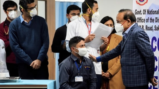 Union Health Minister Harsh Vardhan interacts with sanitation worker as he becomes the first person to receive Covid-19 vaccine jab at AIIMS, in New Delhi on Saturday. (ANI Photo)