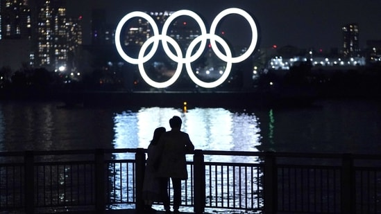 People watch illuminated Olympic rings floating in the waters off Odaiba island in Tokyo, Japan, on Thursday, Jan. 14, 2021. While Japan�s infection count has been well below other rich industrialized nations, the pandemic has been a persistent cloud over the Olympics since they were delayed almost a year ago. Photographer: Toru Hanai/Bloomberg(Bloomberg)