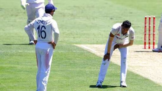 India's Navdeep Saini, right, reacts after injuring his leg while bowling during play on the first day of the fourth cricket test between India and Australia at the Gabba, Brisbane, Australia, Friday, Jan. 15, 2021. (AP Photo/Tertius Pickard)(AP)
