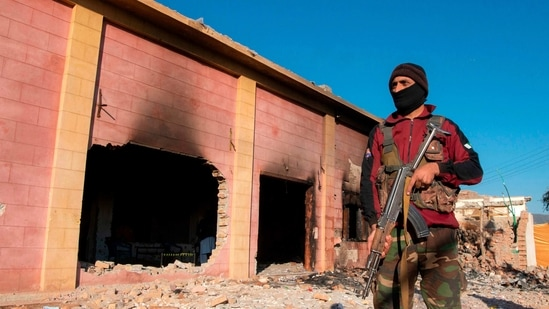 A policeman stands guard at the burnt Hindu temple in Karak district, Peshawar. On Dec 31, 2020, Hundreds of Muslims attacked and set fire to the temple. (AFP)