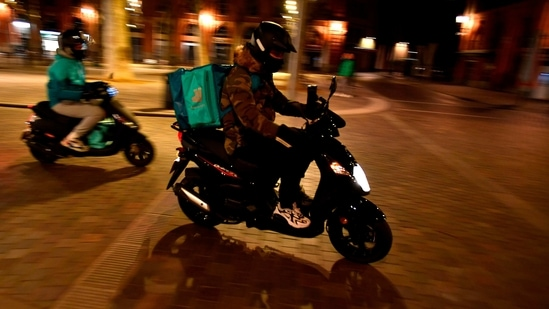 A Deliveroo food delivery scooter drives through a deserted Place Saint Pierre in the city of Toulouse.(AP)
