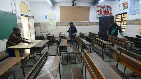 Workers sanitise a classroom at a school for its re-opening from Jan. 18 for classes 10th and 12th, in east Delhi. (PTI)