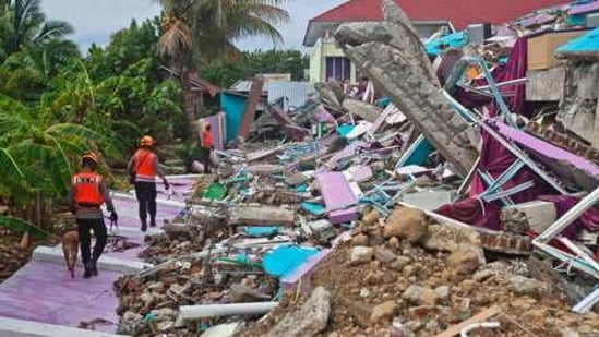 Members of police K-9 squad lead a sniffer dog during a search for victims at a hospital building collapsed in Friday's earthquake in Mamuju, West Sulawesi, Indonesia, Sunday, Jan. 17, 2021. Rescuers retrieved more bodies from the rubble of homes and buildings toppled by the 6.2 magnitude earthquake while military engineers managed to reopen ruptured roads to clear access for relief goods. (AP Photo/Yusuf Wahil)(AP)