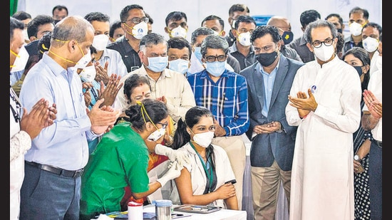 A medic administers the first dose of Covishield vaccine to Madhura Patil in the presence of Maharashtra Chief Minister Uddhav Thackeray at BKC. (Pratik Chorge/HT Photo)