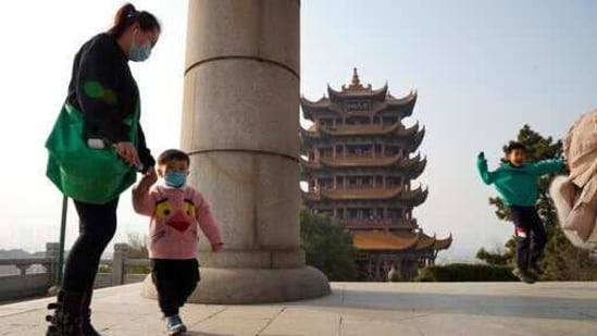Visitors wear masks as they visit the iconic Yellow Crane Tower, a popular tourist site in Wuhan.(AP Photo)