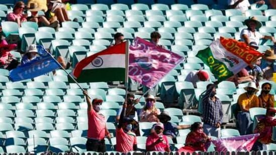 Indian supporters wave flags during play on day four of the third cricket test between India and Australia at the Sydney Cricket Ground, Sydney, Australia, Sunday, Jan. 10, 2021. (AP Photo/Rick Rycroft)(AP)