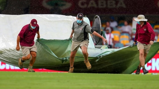 Brisbane: Ground staff bring covers onto the field as the rain stops play on day four of the fourth cricket Test between India and Australia at the Gabba, Brisbane(AP)