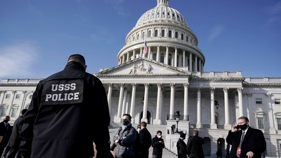 High-level security officials make a survey of the East Front of the Capitol after an announcement of security problems during inauguration rehearsal.(AP)