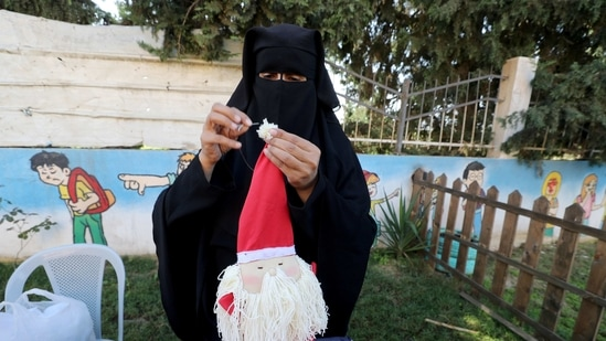 A Palestinian woman wearing face veil, niqab, works on a Christmas-themed doll in a handicraft workshop.(Representational Image / REUTERS)