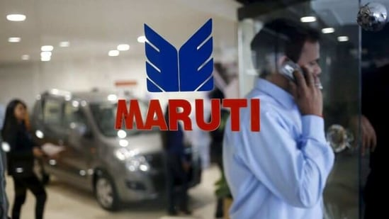 A man speaks on his mobile phone as he exits a glass door with the logo of Maruti Suzuki India Limited at a showroom in New Delhi, India.(Reuters)