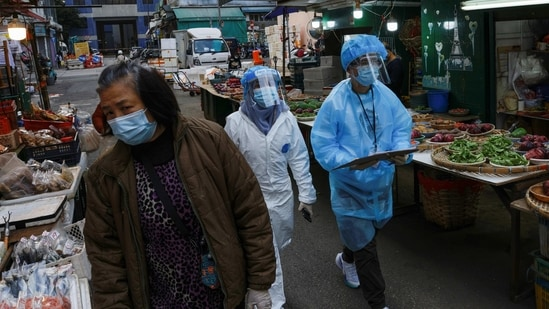 Medical workers in protective suits walk near the residential area at Jordan, after the expand of mandatory coronavirus disease (Covid-19) testing, in Hong Kong, China.(Reuters)