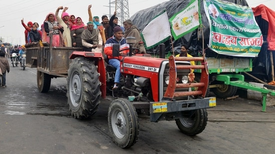 Farmers raise slogans as they ride tractor during an ongoing protest against the new farm laws, at the Delhi-Ghazipur border on Monday.(ANI Photo)