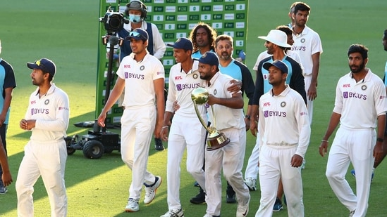 Indian players celebrate with their trophy after defeating Australia by three wickets on the final day of the fourth cricket test at the Gabba, Brisbane, Australia, India won the four test series 2-1.(AP)