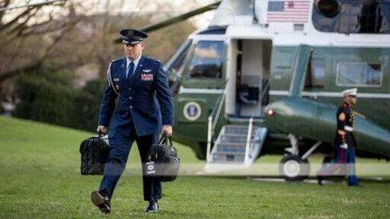 "A US military aide carries the ""president's emergency satchel,"" also know as ""the football,"" with the nuclear launch codes.(AP)"