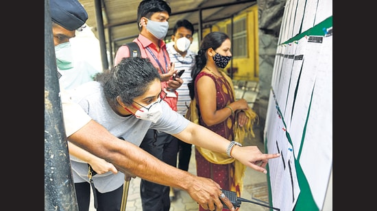 Healthcare workers check the details on the notice board before the vaccination process at Rajawadi Hospital on Tuesday. (Satish Bate/HT Photo)