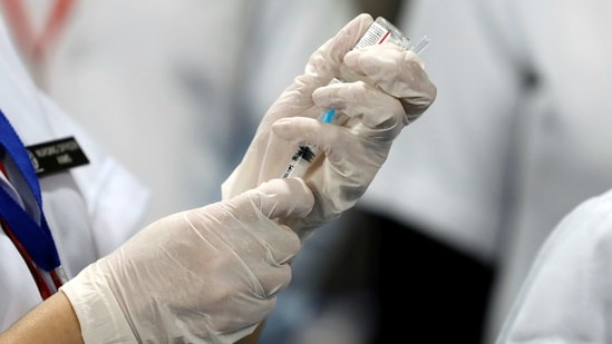 A healthcare worker fills a syringe with a dose of Cpovid-19 vaccine(Reuters File Photo )