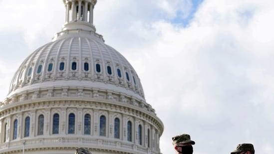 National Guard troops receive guns and ammunition outside the US Capitol building.(REUTERS)