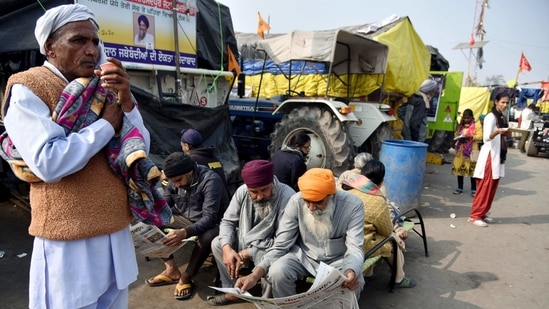 Farmers take rest during a protest against farm bills at Singhu Border in New Delhi on Tuesday. (ANI Photo)