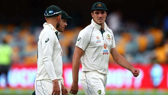 Australia's Pat Cummins (R), Tim Paine (C) and Nathan Lyon walk off the field as rain stop the play during the day four of the fourth cricket Test match between Australia and India at The Gabba in Brisbane on January 18, 2021. (Photo by Patrick HAMILTON / AFP) / --IMAGE RESTRICTED TO EDITORIAL USE - STRICTLY NO COMMERCIAL USE--(AFP)