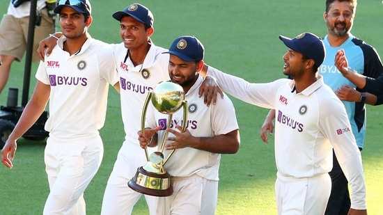 India's Rishabh Pant carries the trophy as he celebrates with his teammates after defeating Australia.(AP)