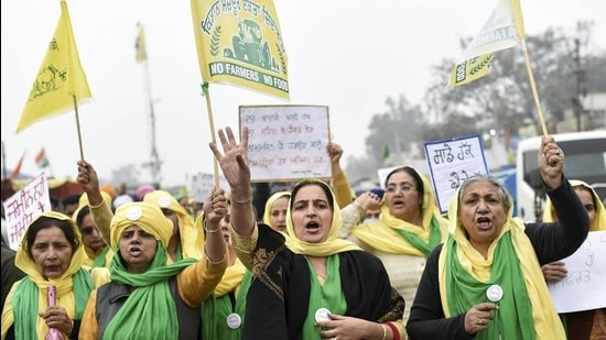 Women raise slogans during the farmers' protest against new farm laws, at Singhu border in New Delhi, Monday. (PTI)