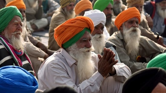 Farmers sitting during an ongoing protest against the new farm laws, at Singhu border in New Delhi. (ANI Photo)