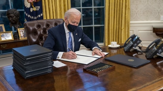 U.S. President Joe Biden signs executive orders in the Oval Office of the White House in Washington, D.C., U.S., on Wednesday.(Bloomberg Photo )