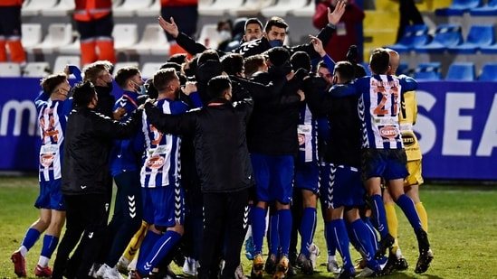 Alcoyano players celebrate after knocking out Real Madrid during a Spanish Copa del Rey round of 32 soccer match between Alcoyano and Real Madrid at the El Collao stadium in Alcoy, Spain, Wednesday Jan. 20, 2021.(AP)