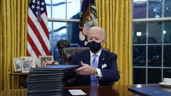 President Joe Biden signs his first executive orders in the Oval Office of the White House on January 20 in Washington, DC. (AP)