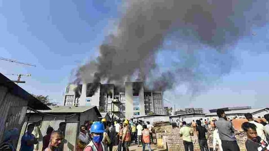 Workers rush out of the building after fire breaks out at Serum Institute of India, Pune, on Thursday. (PTI)