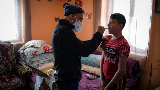 Valeriu Nicolae shows a boy how to correctly brush his teeth in Nucsoara, Romania, Saturday, Jan. 9, 2021. A gentle hero to many in Romania, Valeriu Nicolae says that, at heart, he is more like former NBA star Michael Jordan — highly competitive and eager to improve in what he does best. In Nicolae's case that is helping others. The rights activist has earned praise for his tireless campaign to change for the better the lives of the Balkan country's poorest and underprivileged residents, particularly the children. (AP Photo/Andreea Alexandru)(AP)
