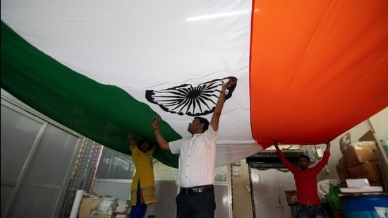Workers inspecting a large Indian tricolour after stitching it ahead of Republic Day. (HT Photo)