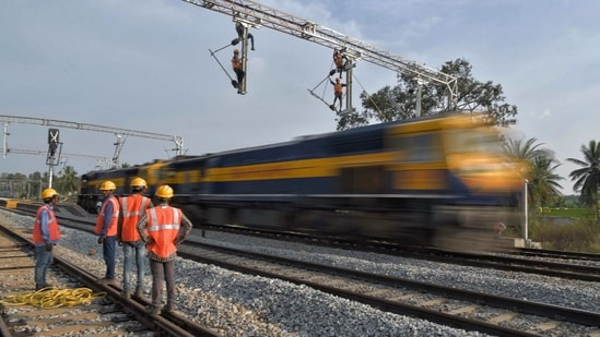 Workers on contract for Indian Railways, erect infrastructure for drawing electric cable lines over railway tracks for use by locomotives on the outskirts of Bangalore on January 15, 2021. (Photo by Manjunath Kiran / AFP)(AFP)