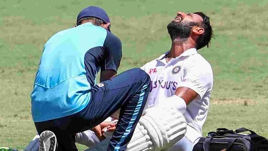 India's Cheteshwar Pujara reacts as he receives treatment after he is hit while batting during play on the final day of the fourth cricket test between India and Australia at the Gabba.(AP)