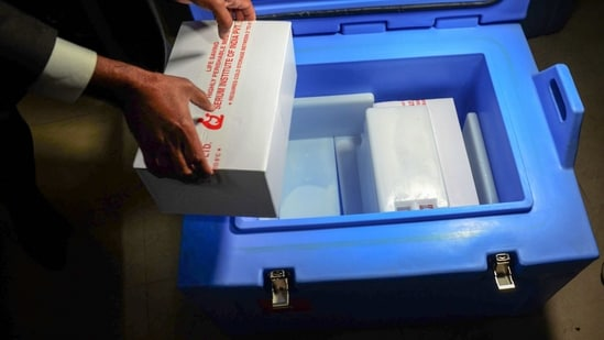 A health official holds a box containing Covishield vaccine doses in Amritsar.(PTI)