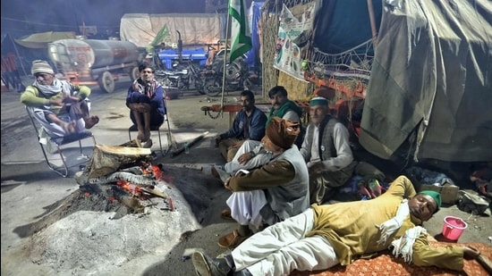 Farmers sit next to a bonfire during their protest against farm law, at the Ghazipur border in New Delhi on Thursday. (ANI)
