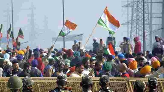 Farmers hold flags as police personnel stand guard behind barricades during protests against new farm laws at Ghazipur (Delhi-UP border) (Sakib Ali / HT Photo).