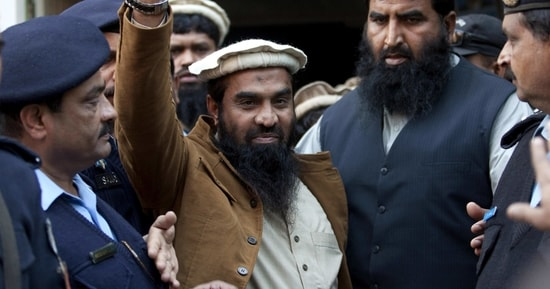 Police officers escort Zaki-ur-Rehman Lakhvi, center, the main suspect of the Mumbai terror attacks in 2008, after his court appearance in Islamabad, Pakistan.(AP Photo)