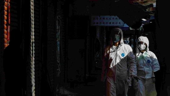 Health workers wear protective gear inside a locked down portion of the Jordan residential area to contain a new outbreak of the coronavirus disease (COVID-19), in Hong Kong, China January 23, 2021. REUTERS/Tyrone Siu(REUTERS)