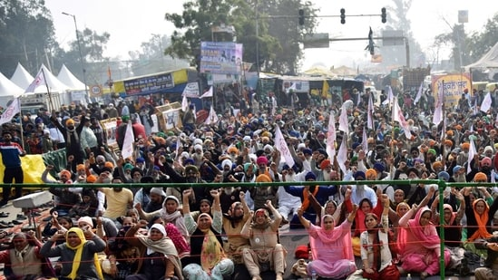 Farmers raise slogans during an ongoing protest against the new farm laws, at the Singhu border in New Delhi.