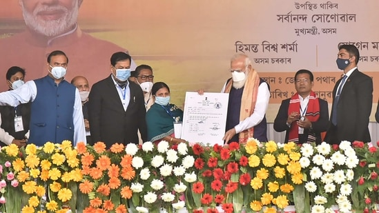 Prime Minister Narendra Modi distributes 'Land Patta' to a woman during a public meeting, at Jerenga Pathar in Sivasagar District of Assam. (PTI Photo)