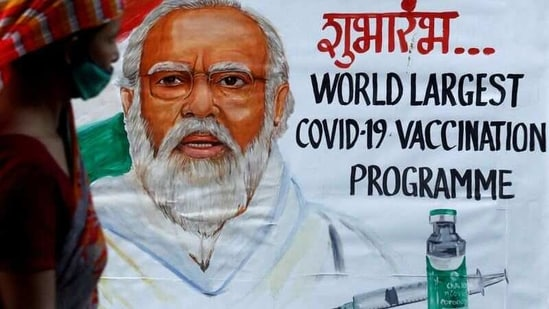 A woman walks past a painting of Indian Prime Minister Narendra Modi a day before the inauguration of the Covid-19 vaccination drive on a street in Mumbai, India, January 15, 2021. (REUTERS)