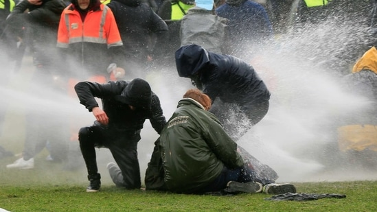 Police uses a water canon during a protest against restrictions put in place to curb the spread of the coronavirus disease in Amsterdam, Netherlands on January 24, 2021. (REUTERS)