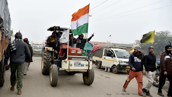 A farmer drives a tractor with the national flag as farmers prepare for a tractor rally on January 26, at Singhu Border near Delhi on Sunday. (ANI Photo)