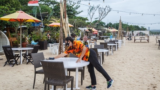An employee wearing a protective mask cleans a table at a restaurant in Kedonganan, Bali, Indonesia,. (Bloomberg)