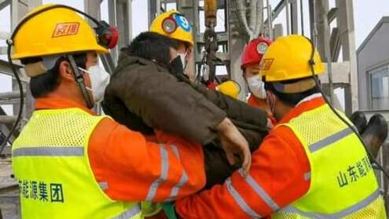 In this photo released by Xinhua News Agency, rescuers carry a miner who was trapped in a gold mine in Qixia City in east China's Shandong Province,(AP)