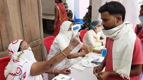Bihar Election Results 2020: Voters undergoing thermal screening at a polling booth as they stand in queues to cast their votes for the second phase of the Bihar Assembly Election, in Begusarai.(ANI)