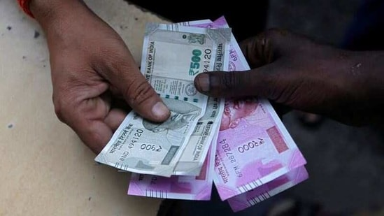 A customer hands Indian currency notes to an attendant at a fuel station in Mumbai, India.(Reuters)