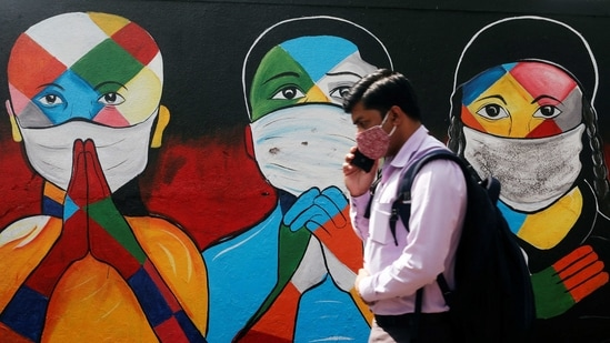 A man walks past graffiti of people wearing protective masks amidst the spread of the coronavirus disease (Covid-19) on a street in Navi Mumbai in this file photo.( Reuters)