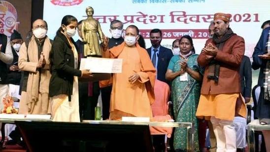 Uttar Pradesh chief minister Yogi Adityanath distributing the certificate during the inauguration of Uttar Pradesh Diwas in Lucknow on Sunday. (ANI Photo)